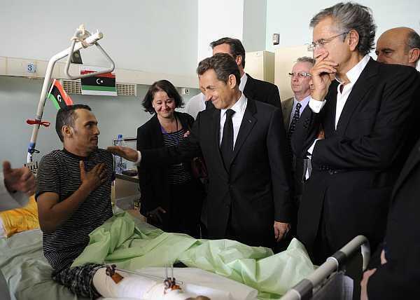 El presidente francés Nicolas Sarkozy, el primer ministro británico (oculto) y el filósofo francés Bernard-Henri Lévy visitan a un hombre herido en el Centro Médico de Trípoli, el 15 de septiembre de 2011.