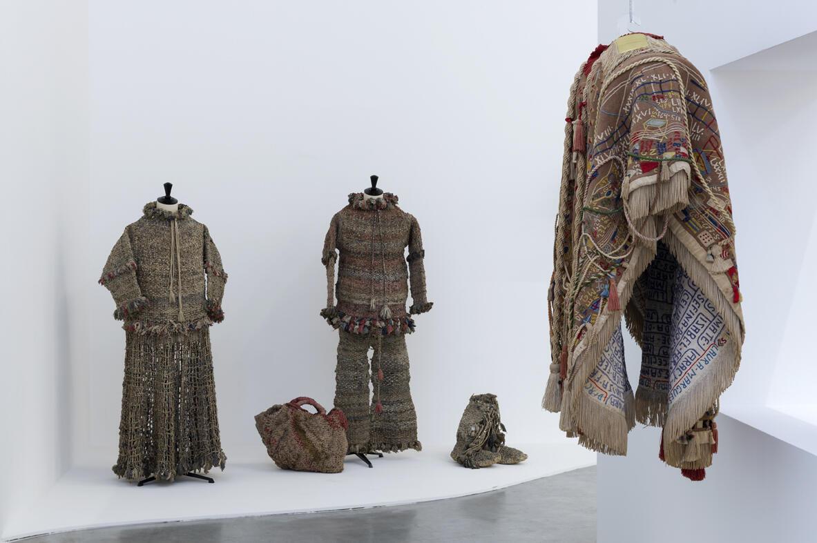 Vista lateral do Manto da Apresentação, diante dos trajes com tiras de pano de chão trançadas, do italiano  Giuseppe Versino