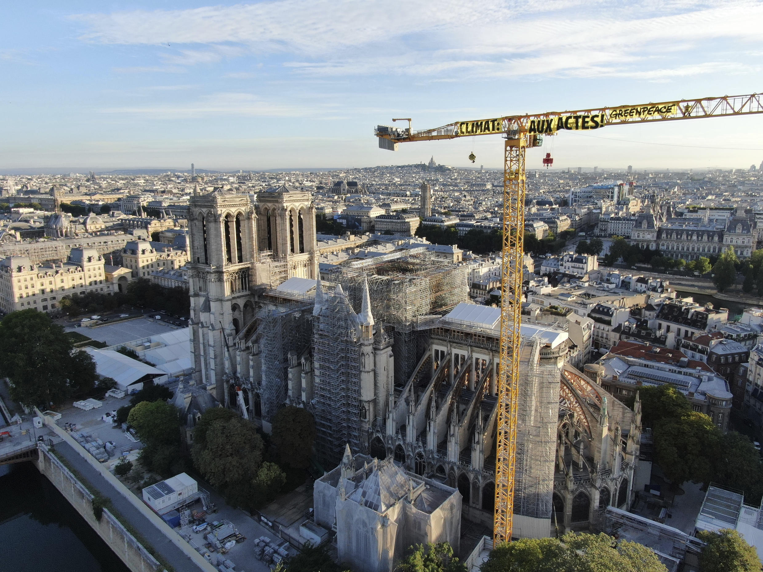 "In this photo provided by Greenpeace, a banner attached to a crane reads: ""Climate. In action"", near Notre Dame Cathedral, in Paris, Thursday, July 9, 2020. Greenpeace activists hung banners from the huge construction crane atop Notre Dame Cathedral in Paris on Thursday accusing France and President Emmanuel Macron of not doing enough to fight climate change. (Greenpeace via AP)"