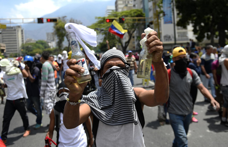 Một người biểu tình thuộc phe đối lập giương hai chai xăng - cocktail Molotov, trong cuộc tuần hành ở Caracas, Venezuela, ngày 01/05/2019