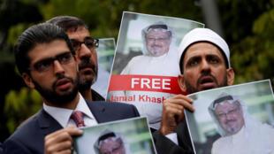 Ativistas de direitos humanos e amigos do jornalista saudita Jamal Khashoggi seguram suas fotos durante um protesto em frente ao Consulado da Arábia Saudita em Istambul, Turquia, em 8 de outubro de 2018.