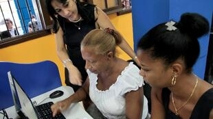 Una empleda de la empresa  cubana de telecomunicaciones  atiende a clientes en un cibercafé.
