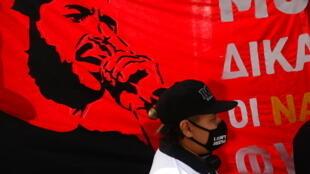 Une bannière représentant le rappeur Pavlos Fyssas, tués par des militants du parti d'extrême droite Aube dorée en 2013, lors d'une manifestation devant la cour pénale d'Athénes, le 7 octobre 2020.