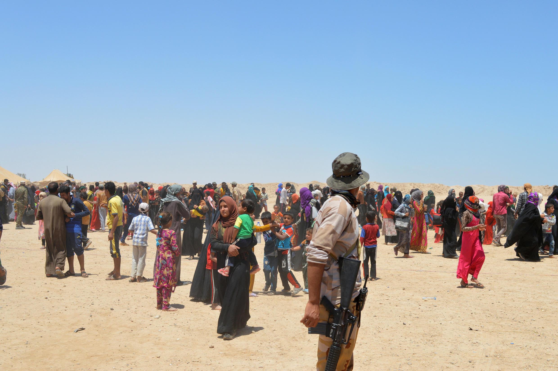 Civis fogem de suas casas na região de Fallujah.