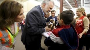 Le Premier ministre du Québec, Philippe Couillard, offre un ours en peluche à une enfant syrien au centre Bienvenue à Montréal.