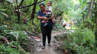 Une femme avec son enfant sur un sentier près de la frontière entre le Nicaragua et le Costa Rica.