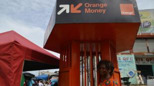 Une femme retire de l'argent à un guichet Orange Money le 20 mai 2015 à Abidjan. Ce système de paiement basé sur un téléphone mobile permet aux clients d'utiliser leur téléphone pour payer leurs factures ou virer des fonds à un autre abonné du téléphone.