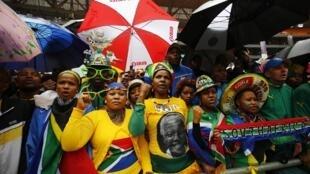 2013年12月10日,南非民众冒雨在索维托体育场等待向曼德拉告别仪式开始。