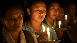 Tibetan refugees light candles during a tribute session for Tibetans who killed themselves through self-immolation