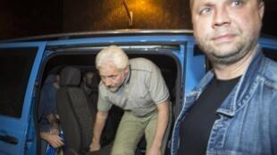 Освобожденные наблюдатели ОБСЕ выходят из машины под строгим оком Александра Бородая, 28 июня 2014.