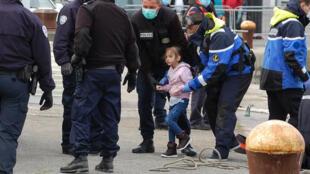 Policías franceses con mascarillas ayudan a una niña de un grupo de migrantes que trató de cruzar el Canal de la Mancha para llegar a Inglaterra, el cual incluía a otros cuatro niños y un bebé, el 16 de mayo de 2020 en Calais, al noroeste de Francia