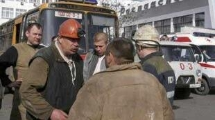 Rescuers and miners talk at the administrative building of Raspadskaya mine