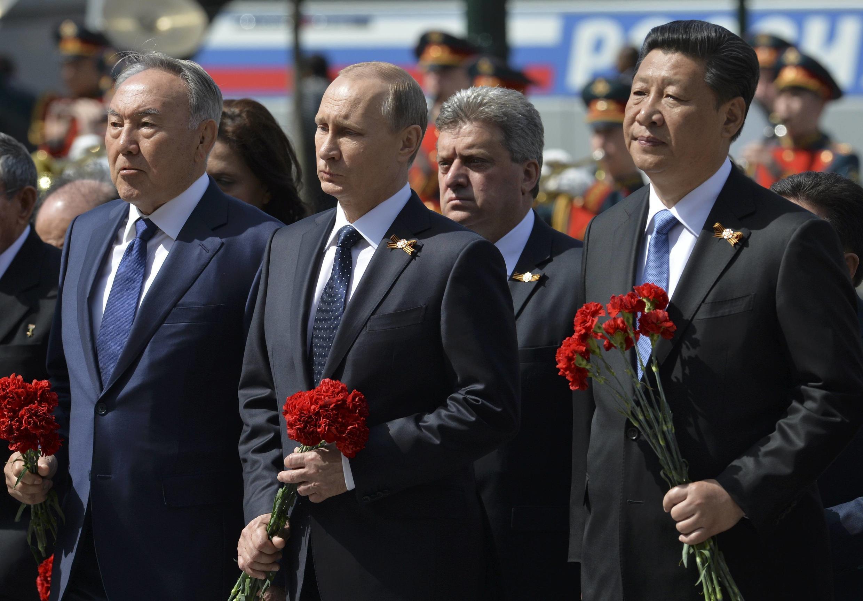 O presidente Vladimir Putin (centro) ao lado do presidente chinês, Xi Jinping, (à dir.) e do presidente do Azerbaijão, Nursultan Nazarbayev, (à esq.), em Moscou.