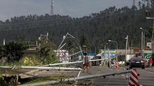 Un homme passe à côté d'un poteau électrique tombé après le passage du typhon dans la ville de Camalig. Le 3 décembre 2019.