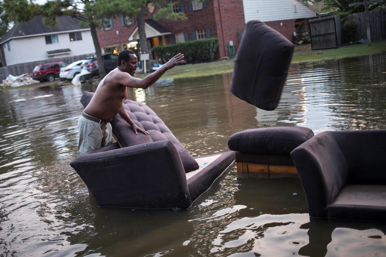 Un habitant de Houston; au Texas, ville également touchée par l'ouragan Harvey, déplace son canapé dans un des quartiers de Houston touchés par l'ouragan Harvey, le 3 septembre 2017.