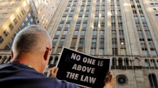 """Một người phản đối hành động của tổng thống Mỹ sau tiết lộ nội dung cuộc điện đàm Trump-Zelensky (""""Không ai đứng trên pháp luật""""), New York, ngày 26/09/2019."""