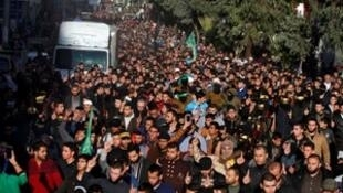 Mourners and Palestinian Hamas militants take part in the funeral of their comrade, who was killed in an Israeli airstrike, in Gaza City December 9, 2017.