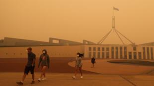 Des passants devant le Parlement à Canberra obligés de porter des masques à cause de la pollution de l'air provoquée par les incendies, le 5 janvier 2020.