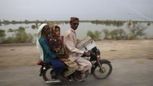 Une famille fuit les inondations, le 9 août 2010.