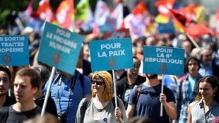 "Protesters hold placards declaring ""For peace"" and ""For human progress"" on the Paris rally on Saturday"