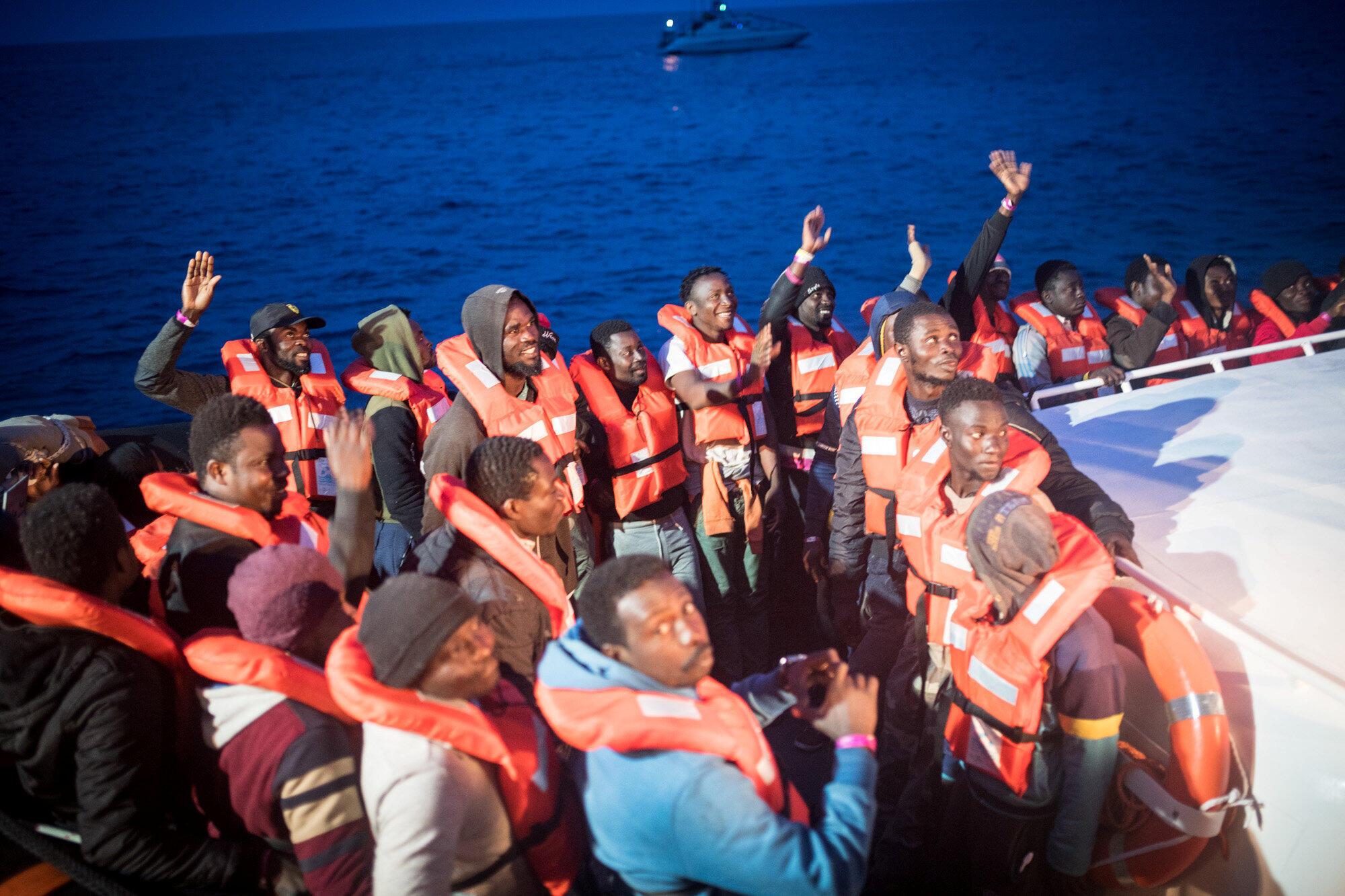 Des migrants transférés du navire humanitaire Sea Watch 3 vers un navire de la marine italienne se dirigeant vers l'île de Lampedusa, en Italie, le 19 mai 2019.