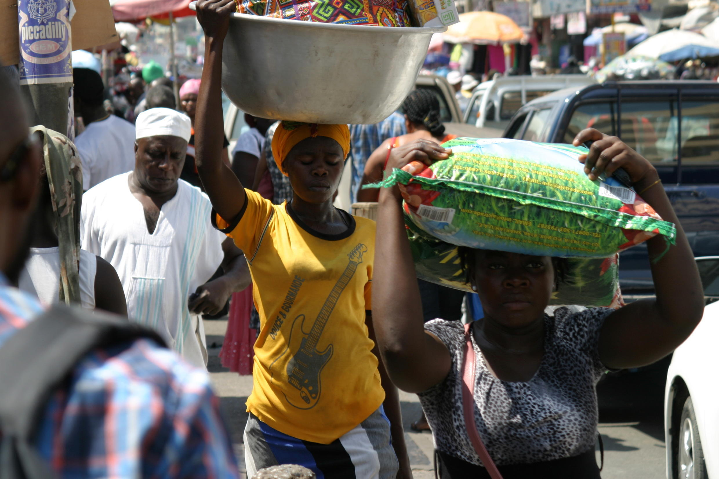 Shoppers at Makola market carry home their purchases.