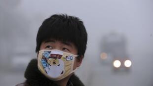 Homem protege o rosto com uma máscara diante da poluição em Bozhou.
