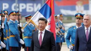 Le président chinois Li Jinping (g) passe en revue la garde d'honneur accompagné par le président serbe Tomislav Nikolić, à Belgrade, le 18 juin.