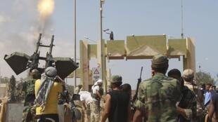 Rebeldes comemoram a tomada de um dos portais de Sirte, ao leste da cidade.