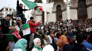 Des gens arborent des drapeaux nationaux lors d'une manifestation appelant le président Abdelaziz Bouteflika à démissionner, à Alger, en Algérie, le 26 mars 2019.