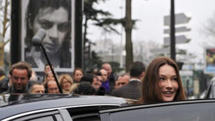 Carla Bruni-Sarkozy is seen in front of a poster showing Benjamin Biolay.