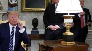 دونالد ترامپ در دفتر کار خود در کاخ سفید. مایک پمپئو، وزیر امور خارجۀ آمریکا، و جان بولتون، مشاور امنیت ملی، پشت سر او ایستادهاند - ٢٠ ژوئن ٢٠١٩