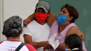 A man helps a sick woman enter a hospital in Guayaquil, Ecuador on April 1, 2020