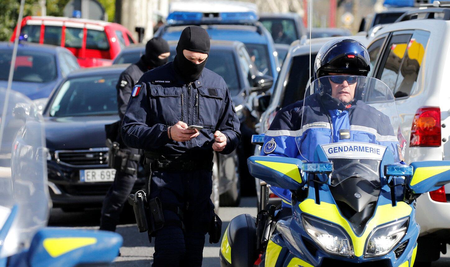 Спецназовец и жандарм недалеко от супермаркета в городе Треб на юге Франции, где произошел захват заложников, 23 марта 2018 г.