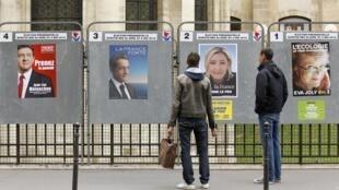 Cidadãos olham cartazes de candidatos à presidência francesa em seção de votação, em Paris. O voto não é obrigatório na França.
