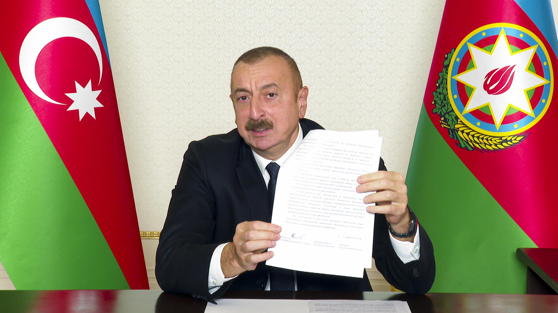 Rais wa  Azerbaijani Ilham Aliyev akionyesha mkataba aliotia saini na taifa la Armenia, Nov 10 2020.