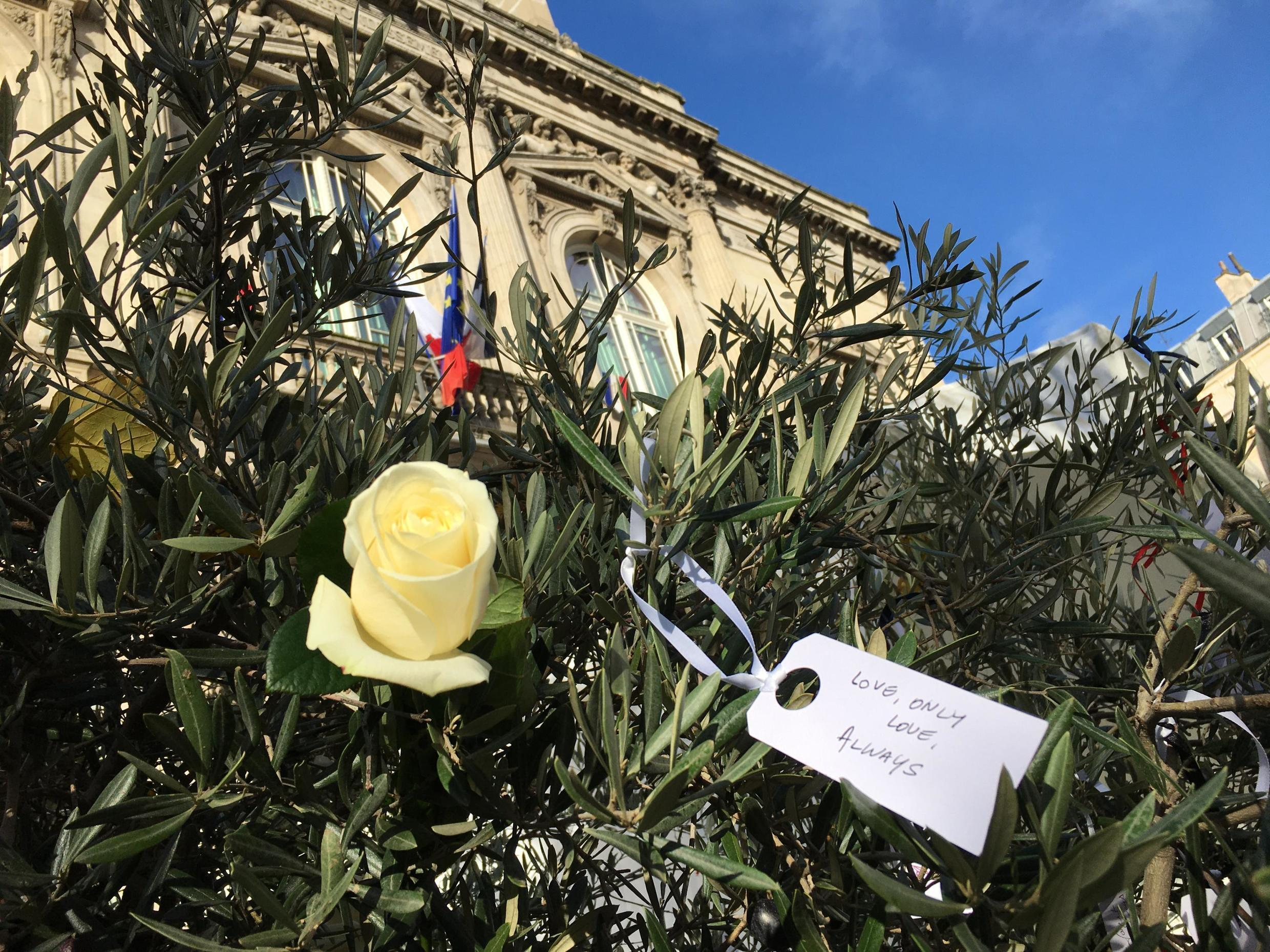 Hundreds of people decorate an olive tree with messages and white roses at a tribute to victims and survivors of 2015 attacks at the Bataclan concert hall, Stade de France stadium and Parisian bars and cafés, 13 November 2019.