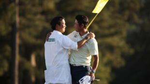 photo d'archives prise le 10 avril 2021 montrant le golfeur japonais Hideki Matsuyama, avec son caddie Shota Hayafuji, sur le green du 18ème trou après avoir remporté le Masters à Augusta, Géorgie, le 11 avril 2021