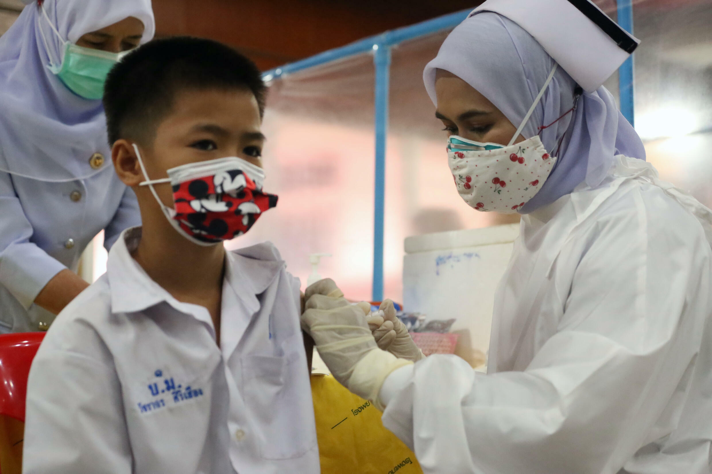 A medical worker administers a dose of the Pfizer vaccine against Covid-19 coronavirus to a school student at a vaccination centre in southern Thailand's Pattani province on October 7, 2021