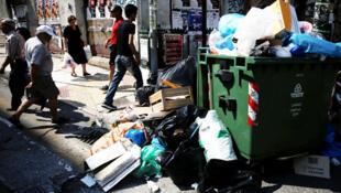 Les gens passent devant une pile de déchets dans Piraeus, près d'Athènes en Grèce, le 26 juin 2017.