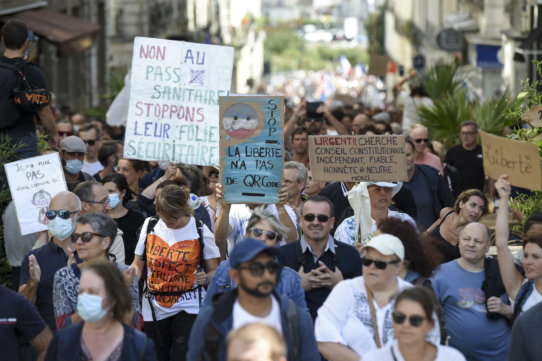 Manifestantes sostienen pancartas en contra del pase sanitario en Francia.