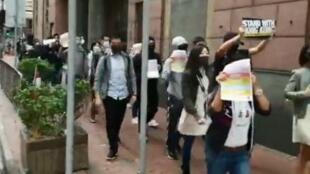 香港市民身穿黑衣步行上班,一邊高呼光復香港等運動口號。