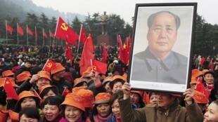 Chinês segura cartaz com foto de Mao Tsé-Tung  durante as comemorações dos 120 anos de nascimento do ex-líder em Shaoshan, sua cidade natal.