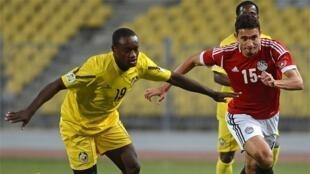 """O defesa moçambicano Zainadine (esquerda) na luta pela posse da bola com o egípcio Mohamed """"Gedo"""" Nagy (direita). Imagem de Arquivo."""