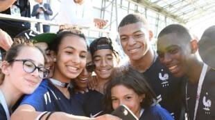 Kylian Mbappé avec un groupe de jeunes supporters à Bondy, le 27 juin 2018.
