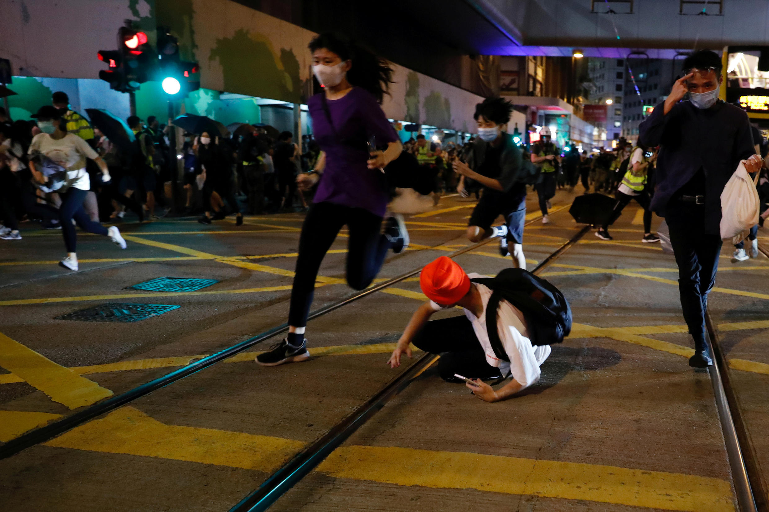 Pro-democracy demonstrators run away as riot police disperse them with pepper-spray pellet during a protest to mark first anniversary of a mass rally against a now-withdrawn extradition bill, in Hong Kong, China June 9, 2020. REUTERS/Tyrone Siu