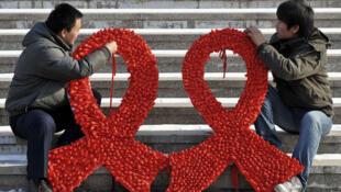 Des étudiants préparent des rubans rouges lors d'une manifestation destinée à lutter contre les discriminations faites aux personnes atteintes du virus du Sida (VIH) à Shenyang, en Chine en novembre 2009.