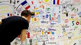 A man visits an exhibition of children's drawing sent at Charlie Hebdo's office after the terrorist attack of January 2015, on June 06, 2018 at Paris' city hall.