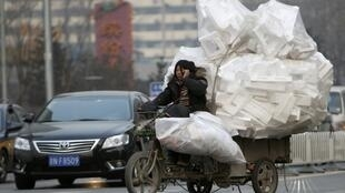 En Chine, une femme utilise son téléphone tout en roulant à moto.