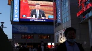 2021年4月16日,在北京的一条购物街上,一块巨大的屏幕显示中国国家主席习近平与德国总理默克尔和法国总统马克龙在参加气候变化视频峰会的画面。